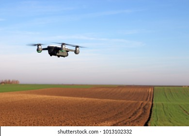 The drone quad copter is flying over the plowed field