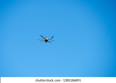 Drone quadcopter with camera against the blue sky
