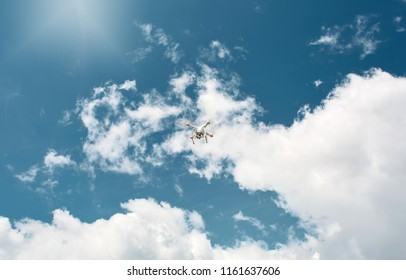 drone quadcopter with digital camera in the blue cloudy sky. quadcopter drone flying with digital camera on the sky.