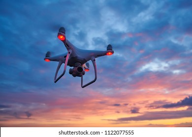 drone quadcopter with digital camera flying at sunset