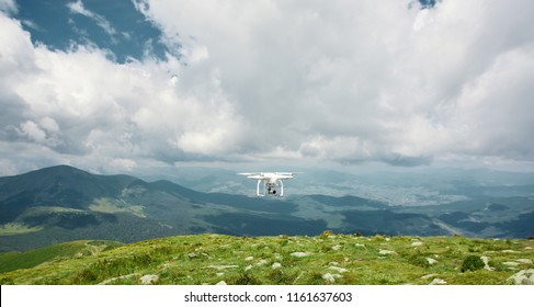 drone quadcopter with digital camera in the mountains. The drone with camera takes pictures of the misty mountains. quadcopter drone flying with digital camera on the sky.