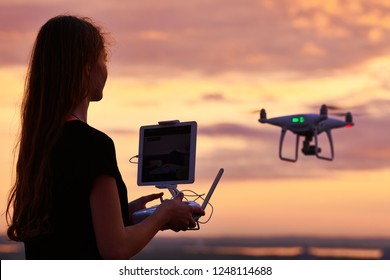 drone quadcopter with digital camera operated by woman at sunset