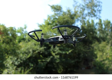 Drone or quadcopter flying with green plants and trees background.
