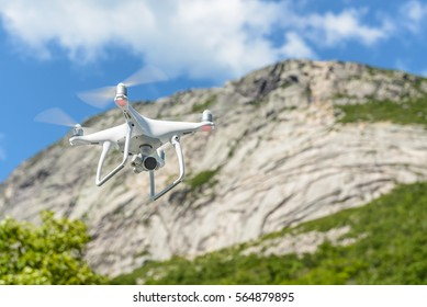 A drone quadcopter hovering in the air with mountains in the background.