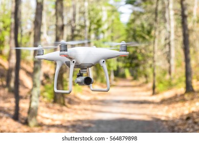 A drone quadcopter hovering in the air on a trail through the woods.