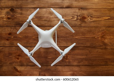 Drone quadcopter on the old wooden background with a copy space. Top view, flat lay composition.
