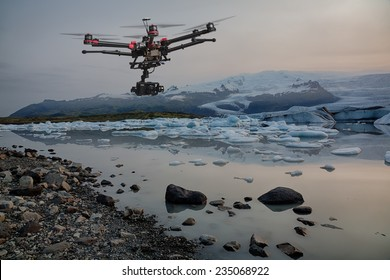 A drone with raised landing gears and a camera flying over icebergs with a glacier in the background