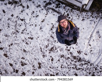 Drone selfie of smiling man from above upside shot in winter snow background