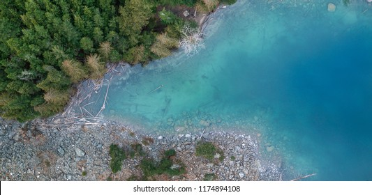 Drone shot of a beautiful glacial fed turquoise blue lake high in the cascade mountains in British Columbia Canada