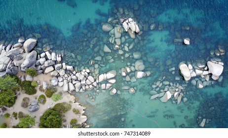 Drone shot of boulders in a crystal blue water in Sand Harbor Beach, Lake Tahoe, Nevada.