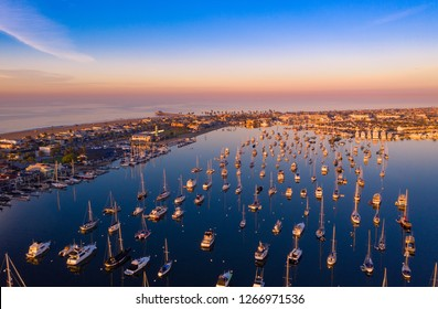 Drone shot of the Newport Beach harbor in Orange County, California early in the morning with boats below.