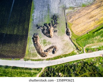 Drone shot of Sinkholes. Huge natural holes in fields after heavy rain. Heart shaped hole on the ground.