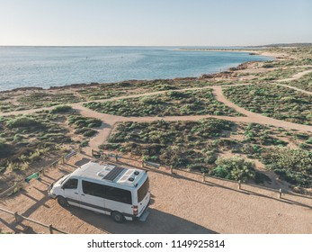 Drone shot of traveling ambulance van with solar panels in front of ocean bay and wild life in Exmouth, Western Australia