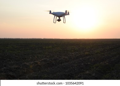 drone silhouette against the background of the sunset. Flying drones in the evening sky.