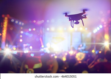 Drone silhouette flying above live concert and shooting photo and video of music festival.