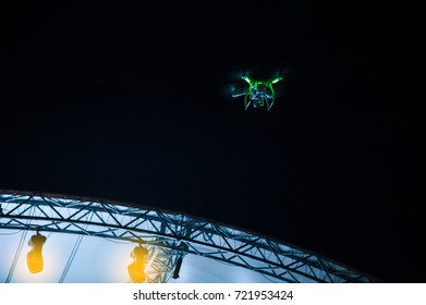 Drone silhouette flying above live concert and shooting photo and video of music festival