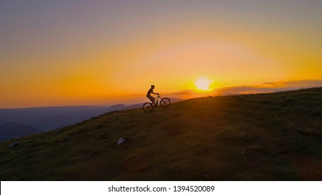 DRONE, SILHOUETTE, SUN FLARE: Unrecognizable cyclist rides an electric bike uphill at golden sunset. Breathtaking shot of an active tourist enjoying a scenic ride in the mountains on an e-bicycle.