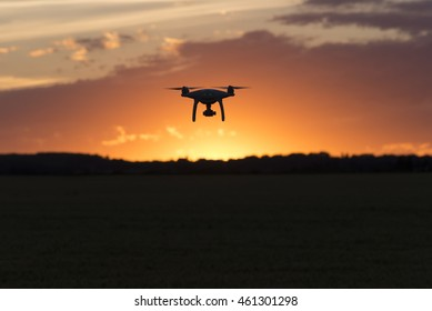 Drone silhouetted against orange sunset