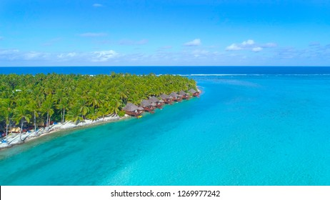 DRONE: Spectacular shot from above of lush tropical island and luxury oceanfront bungalows in Cook Islands. Flying towards the cool overwater villas facing the turquoise ocean in stunning Seychelles