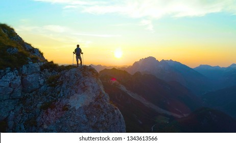 DRONE, SUN FLARE, SILHOUETTE: Unrecognizable male tourist hiking in the Alps observing the sunset. Picturesque shot of the mountains and young hiker being illuminated by a spectacular golden sunrise.