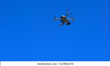 Drone taking off against a bright blue summer sky, with copy space.
