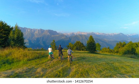 DRONE: Three mountain bikers stop and observe the picturesque morning landscape before exploring the Slovenian countryside. Young tourists riding ebikes stop to look around the scenic evening nature.