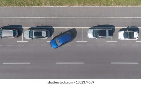 DRONE, TOP DOWN: Flying above a shiny blue car driving out of a roadside parking space. Modern vehicle leaves a parking spot in a long line of parked cars next to an empty city street in Ljubljana.