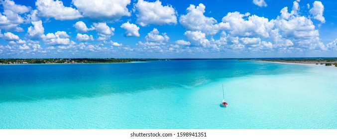 Drone top view of an idyllic scene with a lonely boat in the caribbean in a summer sunny day. Beautiful atmosphere in this not well known oasis becoming a new attraction in Mexico.