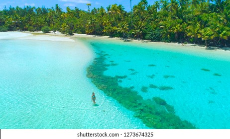 4c3eea42752a DRONE  Tourist girl in blue bikini walks into the shallow turquoise ocean  water surrounding the