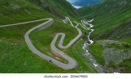 DRONE: Tourists on road trip across the mountains of Switzerland drive along hairpin turns of Gotthardpass. Grey colored tourist car cruises along the scenic switchback road of Passo San Gottardo.