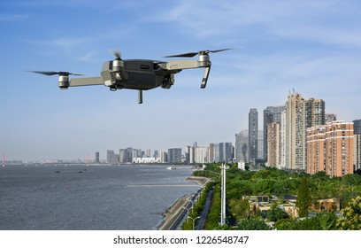 Drone with video camera flying above city