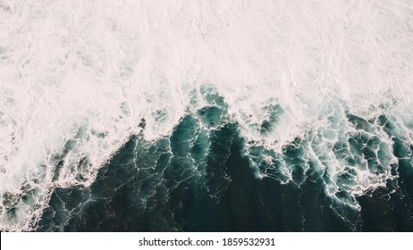 Drone view of amazing waterscape with clear azure sea rolling in sunlight during stormy weather in nature of lagoon outside