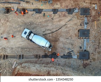 Drone view of a concrete truck and workers on a construction site