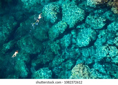 Drone view of a couple snorkeling in tropical sea water