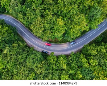 Drone view of a curved road and cars in Transylvania, Romania in a summer day.