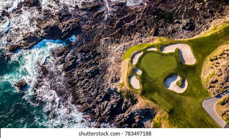 Drone view of a golf course next to the ocean with waves hitting the rocks on the seashore