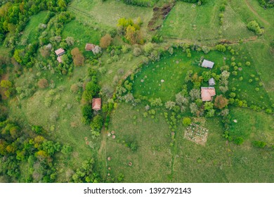 Drone view of green meadows, small houses and roads in Transylvania, Romania.
