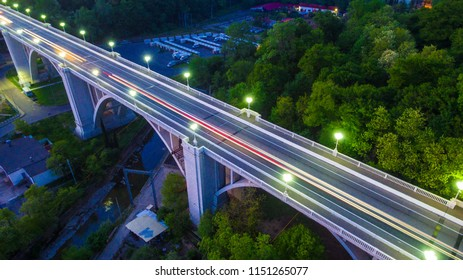 Drone view of the illuminated Matsesta viaduct and mountainside with dense forest at twilight, Sochi, Russia