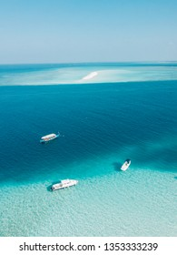 Drone view of the Maldives. You can see a sandbank and different kind of boats. Lost in this paradise between turquoise water and the deep blue of the ocean.