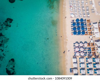drone view of Mykonos island, famous Ornos beach organized with sun beds emerald clear water beach of Ornos in island of Mykonos, Cyclades, Greece - Shutterstock ID 1084091009
