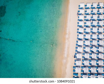drone view of Mykonos island, famous Ornos beach organized with sun beds emerald clear water beach of Ornos in island of Mykonos, Cyclades, Greece