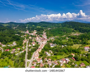 Drone view over the green forest and small city in mountainous area sunny day in summer season. Carpatians mountains, Romania.