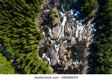 drone view at rapids in a stream in a coniferous woodland in ruggedby landscape of scandinavia