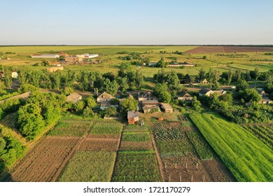 Drone view of rural buildings and agricultural gardens in small village