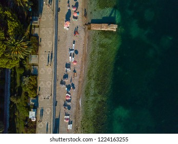 Drone view of Sarande main beach, in Albania, with an amazingly green crystal clear water and sunbeds on the sand while kids playing on a concrete platform during the hot summer on the Balkans.