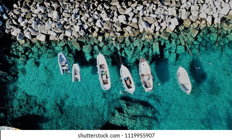 Drone view of small fishermen boats near a rock stone pier.