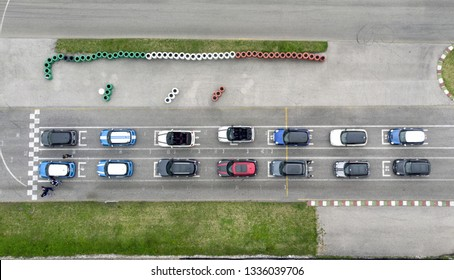Drone view of various colored sports cars ready for departure for a race. Team lined up on the starting grid at the start on a racing circuit. Aerial view of a car race with standard vehicles.