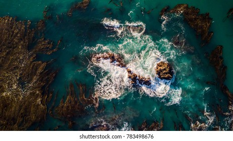 Drone view of waves hitting the rocks on the seashore