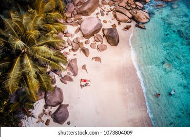 Drone view at the white beach with happy Young couple walking on the beach by the ocean with palmtrees at the Seychelles