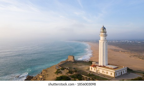 Drone views of the Trafalgar Lighthouse on the Costa de la Luz in Caños de Meca, Cadiz Andalucia, Spain. Faro de Trafalgar from above on a beautiful day with clouds and the blue sea.
